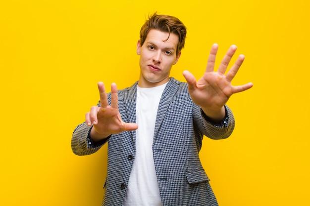 若い赤い頭の男笑顔とフレンドリーな探して、8番または8番を手で前方に表示、オレンジカウントダウン