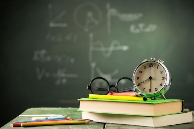 오전 8시 학교 개념으로 돌아가기. 배경에 칠판이 있는 책의 알람 시계