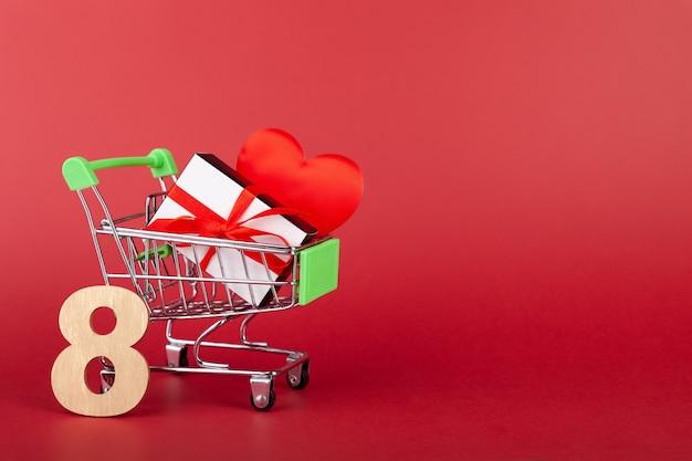 8、ハート、赤い背景のショッピング手押し車の赤いリボン、販売と愛の概念、国際女性の日、バレンタインデー、コピースペース、水平の黒と白のギフトボックス