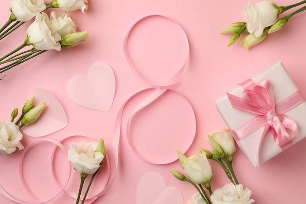 8 из ленты, роз, сердечек и подарочной коробки на розовом фоне, вид сверху