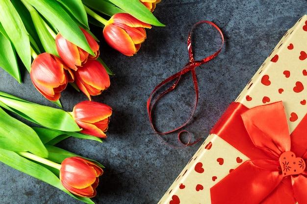 3月8日のコンセプト、チューリップの花の暗い表面、赤いリボンのギフトボックス、ハート、女性の日