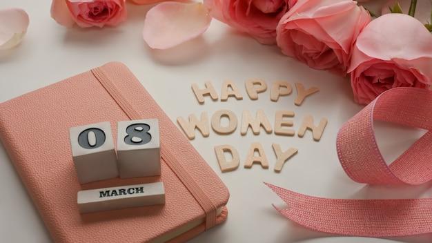 ピンクの花、リボン、ノートブックで飾られた白いテーブルの背景に3月8日幸せな女性の日