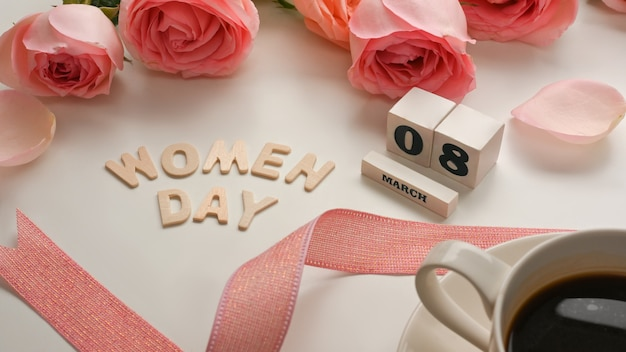 3月8日コーヒーカップ、ピンクのバラの花とリボンと白いテーブルの背景に幸せな女性の日