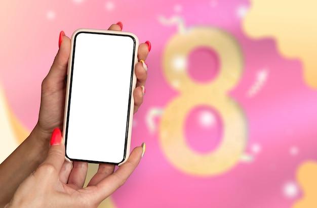8 марта международный женский день. женщина держит в руках макет смартфона на фоне поздравительной открытки.