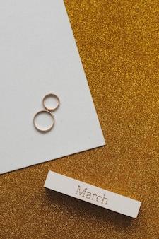3 월 8 일, 장식 요소가있는 국제 여성의 날 배경. 두 개의 금 결혼 반지와 march라는 단어로 만든 여덟.