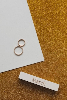 8 march, international women's day background with decor elements.  eight made of two gold wedding rings and word march.