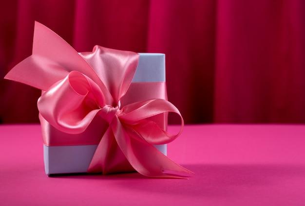 8 марта распродажа шаблон. голубая подарочная коробка и нежный розовый бант на смелом фоне малинового занавеса.