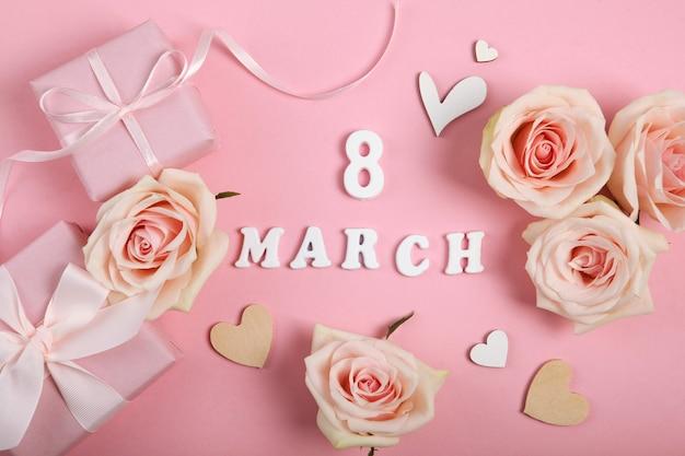 ピンクのギフト、バラ、ピンクの背景に装飾が施された3月8日のテキスト