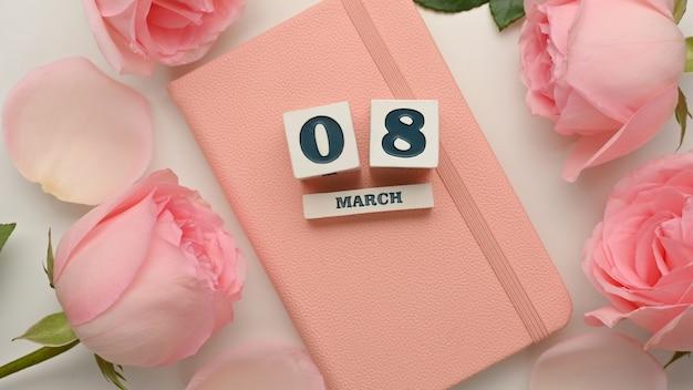 白いテーブルの背景にピンクのバラの花で飾られたピンクの日記の本の3月8日女性の日