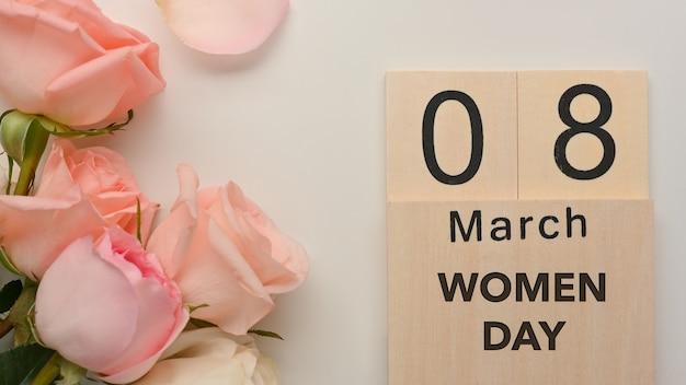 ピンクのバラで飾られた白いテーブルの背景に3月8日女性の日