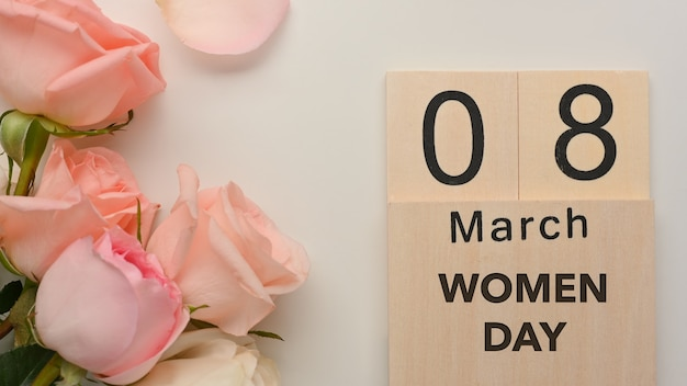 8 march women's day on white table background decorated with pink roses