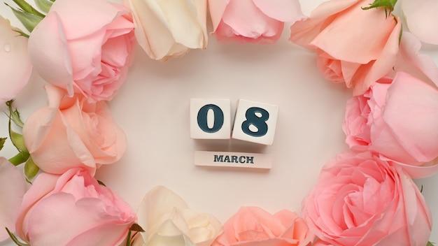 白い背景にピンクのバラの花で飾られた3月8日女性の日