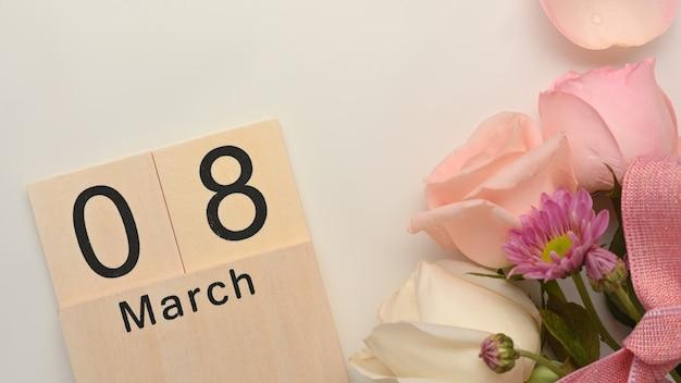 白いテーブルの背景にピンクのバラの花で飾られた3月8日女性の日