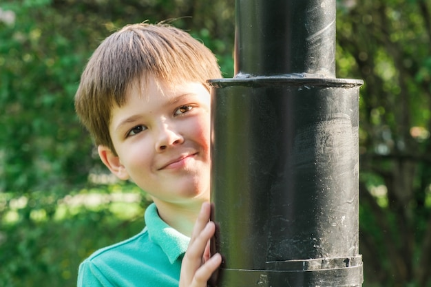 8-year-old boy with dark hair stands behind a metal lamppost. cute brunet boy playing hide and seek behind a lamppost. children play in the park