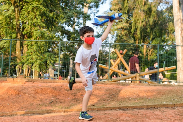 8세 어린이, 한 발로 균형을 잡고 공공 광장에서 파란색 스티로폼 비행기를 들고 있습니다.