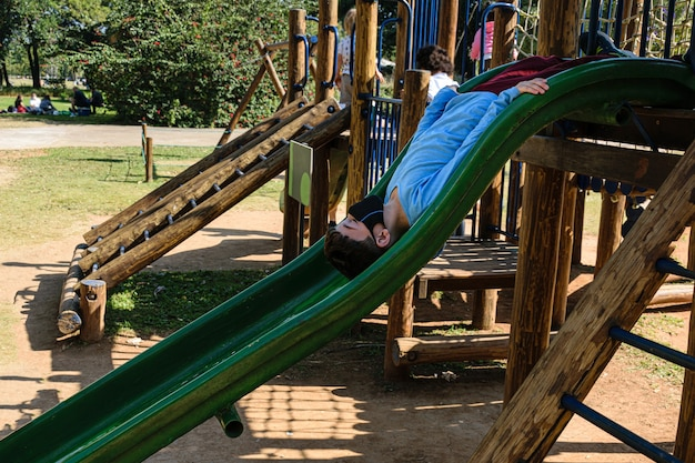 8 year old child in a long-sleeved blue shirt going down a slide upside down.