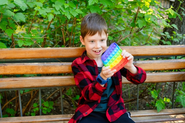 공원에서 뽀삐를 가지고 노는 8세 소년. 장난감으로 행복 한 아이입니다. 밝은 여름 캐주얼 옷을 입은 아이. 여러 가지 빛깔된 팝업 그것을 클로즈업. 안티 스트레스 플라스틱 장난감.