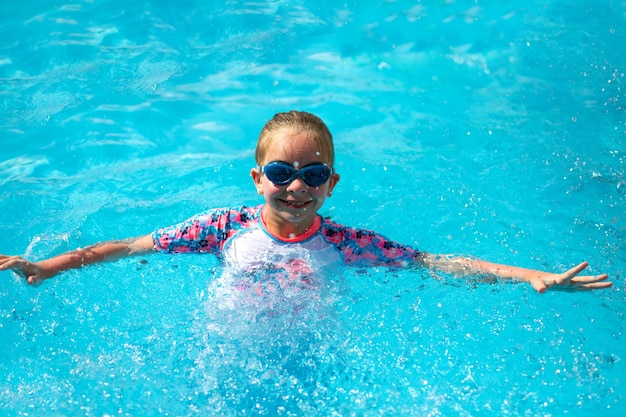 8 years old girl, in a bright swimming suit and blue glasses, stands in the pool under the sun with blue water