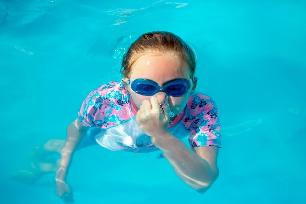 8 years old girl, in a bright swimming suit and blue glasses, swims, dives, dives out from under water in an open-air pool in the sun with blue water