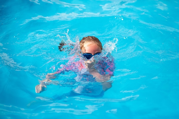8 years old girl, in a bright swimming suit and blue glasses, swims in a pool under the sun with blue water, diving into the water and creating splashes of water