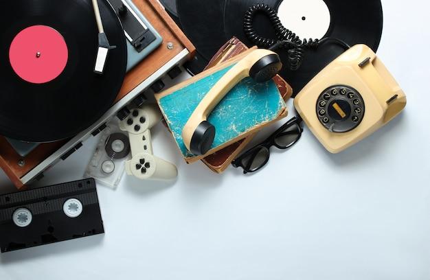 白い背景の上のレトロな80年代ポップカルチャーオブジェクト。コピースペース。回転式電話、ビニールプレーヤー、古い本、オーディオ、ビデオテープ、3dメガネ、ゲームパッド。