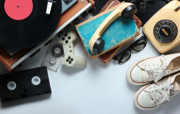 白い背景の上のレトロな80年代ポップカルチャーオブジェクト。コピースペース。スニーカー、回転式電話、ビニールプレーヤー、古い本、オーディオ、ビデオテープ、3dメガネ、ゲームパッド。