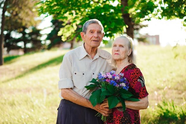 Пожилой мужчина 80 лет дарит цветы своей жене