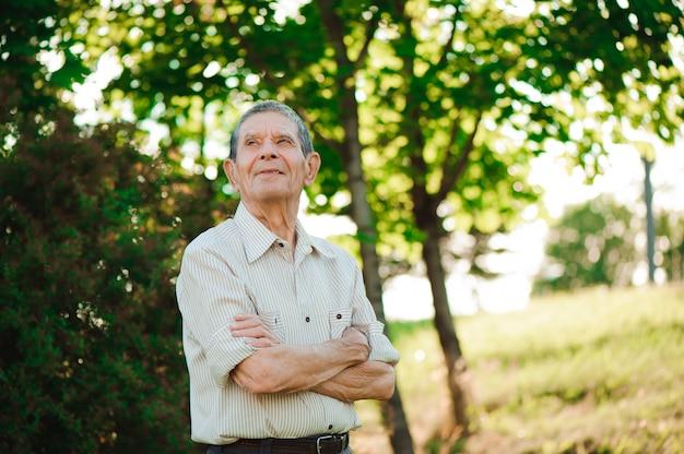 夏の公園でポーズをとって80歳の男。