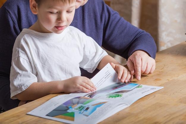 一緒に教育本を読んでいる彼女の孫と自宅で成熟した女性(80歳)の手