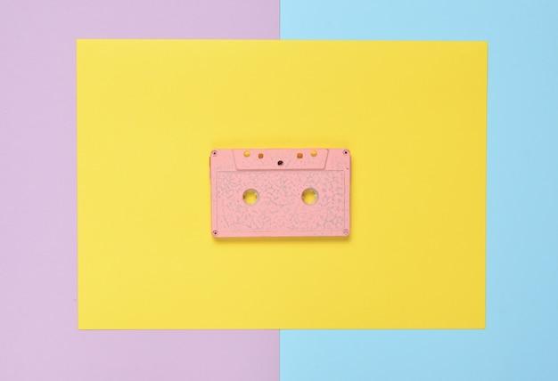色紙の背景にオーディオカセット。レトロメディアテクノロジー80年代。音楽、エンターテイメント。上面図。ミニマリズムの傾向