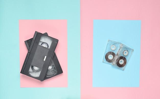 オーディオカセット、ピンクのパステルブルーの背景にビデオカセット。 80年代のレトロな属性。上面図