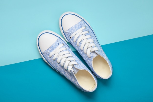 Модные женские кроссовки с белыми кружевами из 80-х на голубом пастельном фоне. вид сверху.