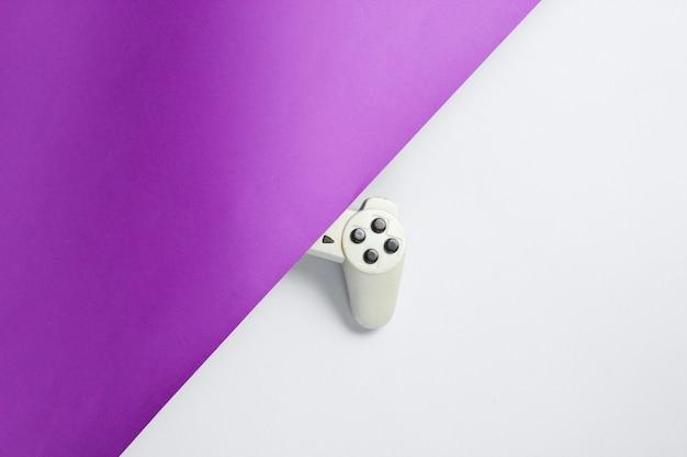 Половина геймпада на пурпурно-сером столе. ретро стиль 80-х. вид сверху