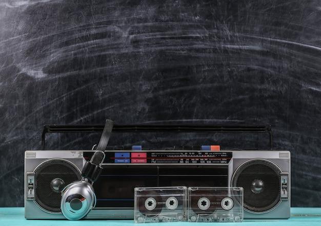 80年代レトロオールドスクールポータブルステレオラジオカセットレコーダー、ヘッドフォン、黒板の背景にオーディオカセット