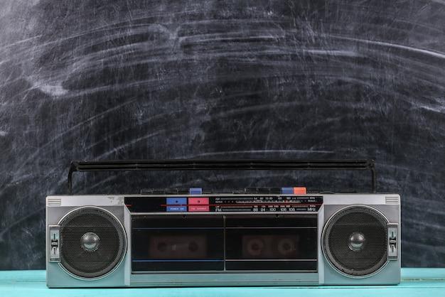 黒板の背景に80年代のレトロな古い学校のポータブルステレオラジオカセットレコーダー