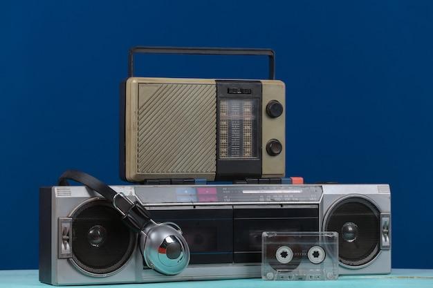 80년대 복고풍의 구식 휴대용 스테레오 카세트 레코더와 라디오 수신기, 헤드폰, 고전적인 파란색 배경의 오디오 카세트. 속성 80년대, 레트로 미디어, 엔터테인먼트