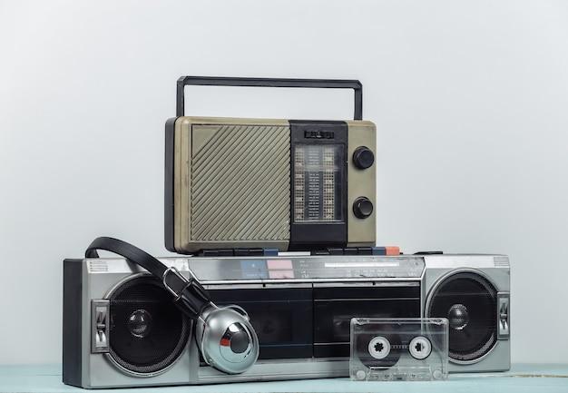 80년대 복고풍의 구식 휴대용 스테레오 카세트 레코더와 라디오 수신기, 헤드폰, 흰색 배경의 오디오 카세트. 속성 80년대, 레트로 미디어, 엔터테인먼트