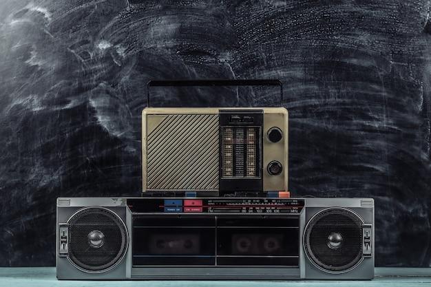 黒板の背景に80年代のレトロな時代遅れのポータブルステレオカセットレコーダーとラジオ受信機