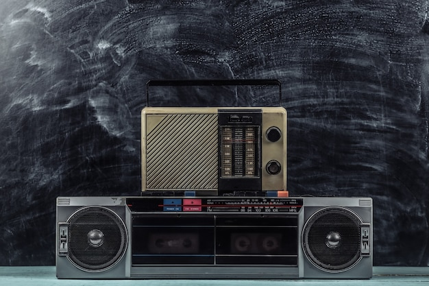 80s retro outdated portable stereo cassette recorder and radio receiver on blackboard background