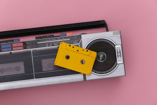 ピンクの背景に80年代のレトロな時代遅れのポータブルステレオラジオカセットレコーダーとオーディオカセット。上面図。フラットレイ