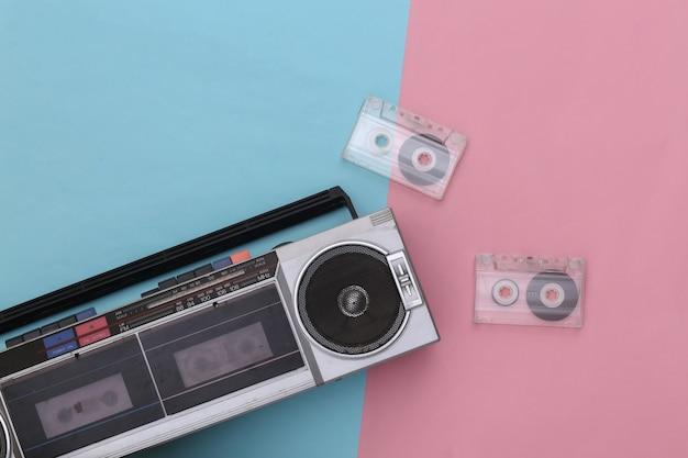 ピンクブルーのパステルカラーの背景に80年代のレトロな時代遅れのポータブルステレオラジオカセットレコーダーとオーディオカセット。上面図。フラットレイ