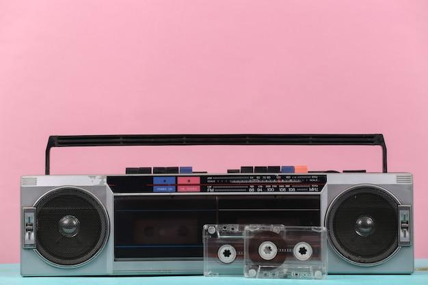 80년대 복고풍의 구식 휴대용 스테레오 라디오 카세트 녹음기와 분홍색 파스텔 배경의 오디오 카세트.