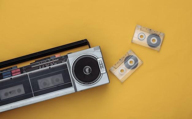 80년대 복고풍의 구식 휴대용 스테레오 라디오 카세트 레코더와 노란색 배경의 오디오 카세트. 평면도
