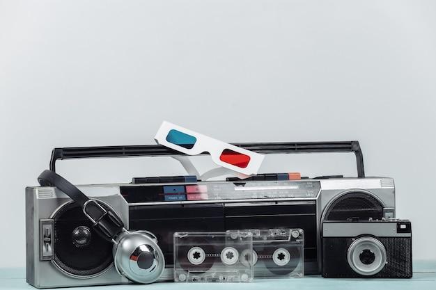80년대 복고풍의 구식 휴대용 스테레오 라디오 카세트 레코더, 헤드폰, 오디오 카세트, 3d 안경, 흰색 배경의 카메라. 속성 80년대, 레트로 미디어, 엔터테인먼트