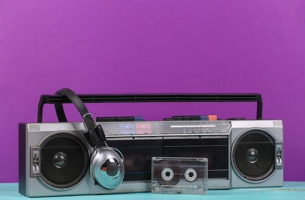 80년대 복고풍의 구식 휴대용 스테레오 라디오 카세트 레코더, 헤드폰, 보라색 배경의 오디오 카세트.