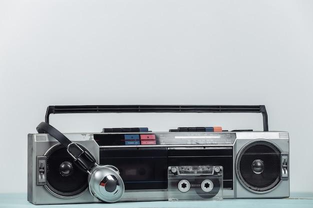 80년대 복고풍의 구식 휴대용 스테레오 라디오 카세트 레코더, 헤드폰, 흰색 배경의 오디오 카세트.
