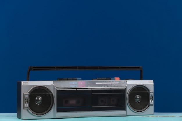 80년대 복고풍의 구식 휴대용 스테레오 라디오 카세트 레코더가 고전적인 파란색 배경에 있습니다.