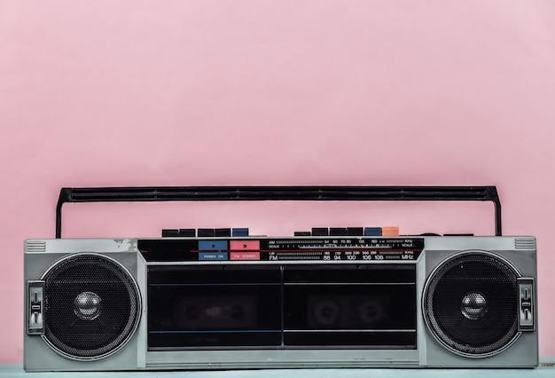 80년대 복고풍의 구식 휴대용 스테레오 라디오 카세트 레코더가 분홍색 파스텔 배경에 있습니다.