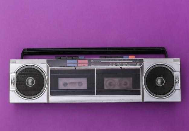 보라색 배경에 80 년대 레트로 구식 휴대용 스테레오 라디오 카세트 레코더. 평면도