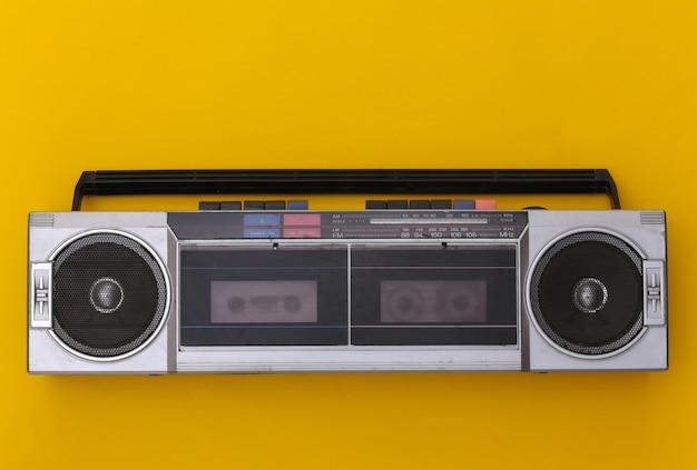노란색 배경에 80 년대 레트로 구식 휴대용 스테레오 라디오 카세트 레코더. 평면도